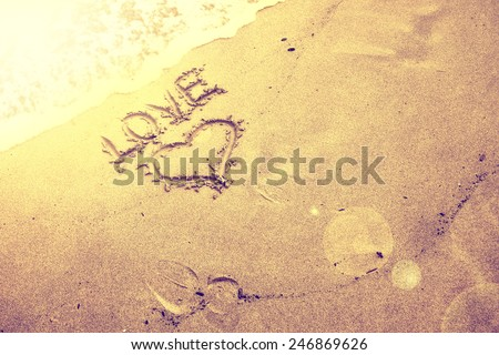 Vintage blurred sunny golden love and heart handwriting sign on sea sand with wave. Gold color filter effect used. - stock photo
