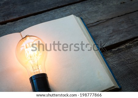 vintage book and light bulb on wood table - stock photo
