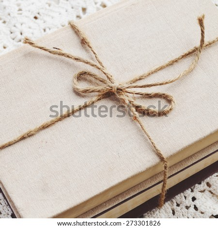 Vintage book bundle tied up with jute twine on lace doily, square  - stock photo