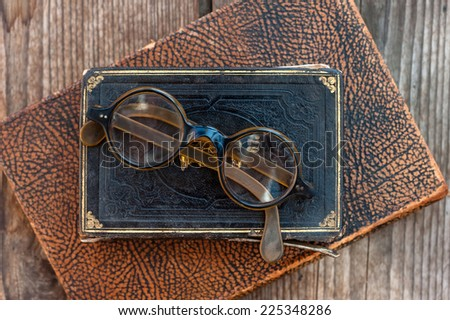 Vintage book, glasses  on the background of a wooden wall. Retro concept - stock photo
