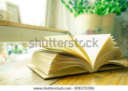 Vintage book on wooden table beside window