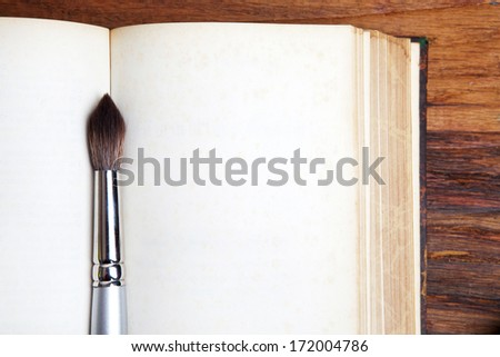 Vintage book, open, on old wooden table with paint brush. - stock photo