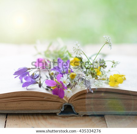 Vintage book with bouquet of meadow flowers, nostalgic vintage background