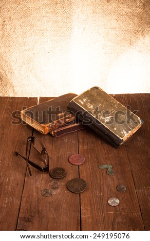 Vintage books and coins and spectacles on old wooden table. Toned