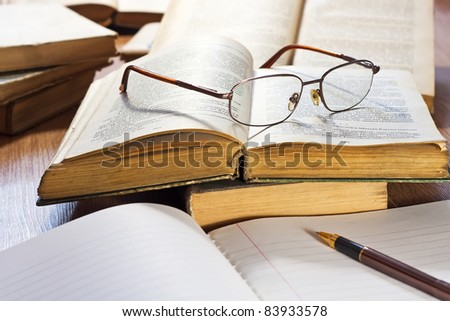 Vintage books and glasses on wooden table - stock photo