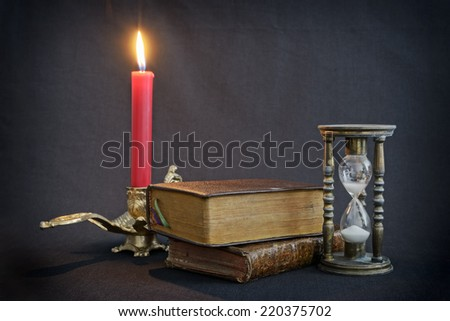 Vintage books and hourglass on dark background with firing red candle - stock photo