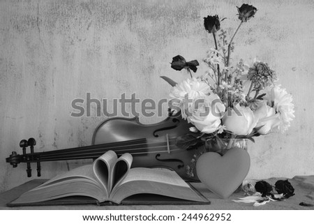 Vintage books and pages love heart sign with violin on grunge sand stone table still life style black and white version - stock photo