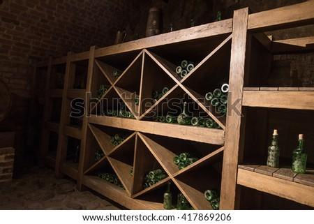 Vintage bottle of wine in a dark basement - stock photo