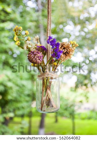 vintage bouquet of dried flowers in a jar - stock photo