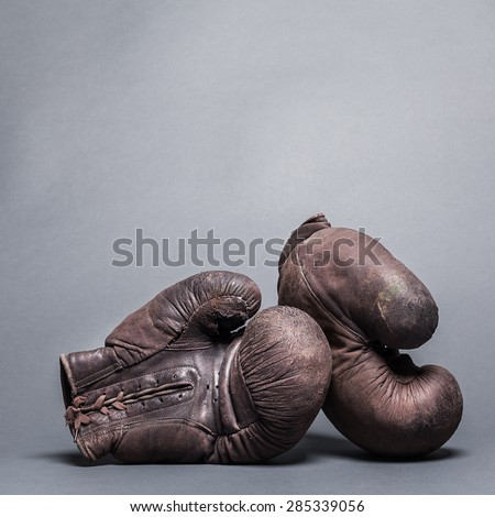 vintage boxing gloves on a gray background - stock photo