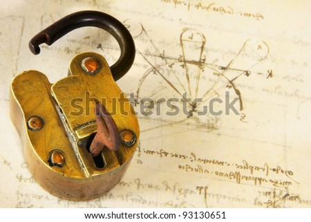 Vintage brass padlock, on copy of very old technical drawing. - stock photo