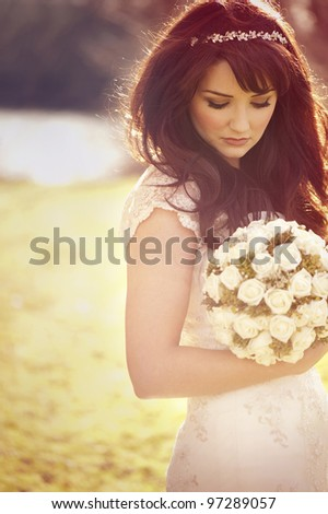 Vintage bride outdoors with bouquet - stock photo
