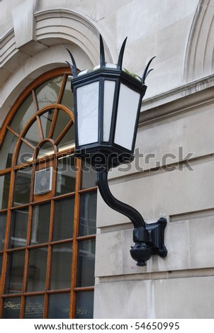 vintage british lamp next to a wooden window - stock photo