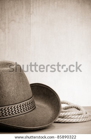vintage brown cowboy hat and rope at wood background on sepia - stock photo