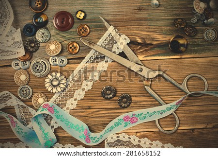 vintage buttons, lace, tape and a dressmaker scissors on a textured surface of old boards. instagram image filter retro style - stock photo