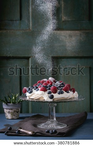 Vintage cake stand with Meringue dessert Pavlova with fresh blackberries and raspberries, strewing by sugar powder. Over blue wooden table. Dark rustic style. - stock photo