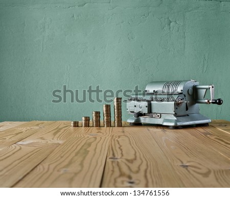 vintage calculator and money against the background of the old wall and wood table - stock photo