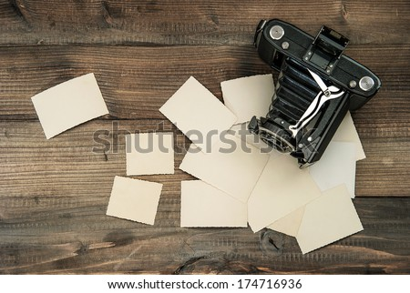 vintage camera and old photos on wooden background. nostalgic style picture - stock photo
