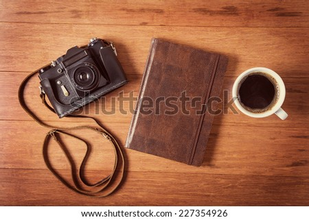Vintage camera, diary and cup pf coffee on wooden table. Instagram style toned photo. - stock photo
