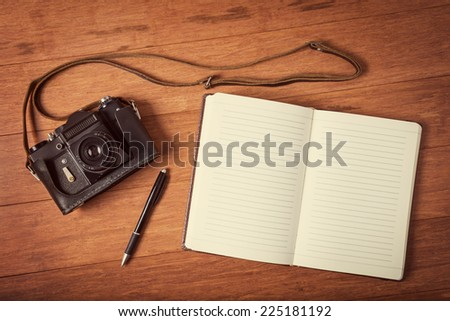 Vintage camera, diary with pan  on wooden table. Instagram style toned photo. - stock photo