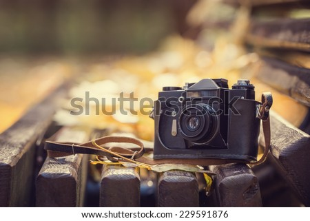 Vintage camera on wooden bench in autumn park. Instagram style toned photo. - stock photo