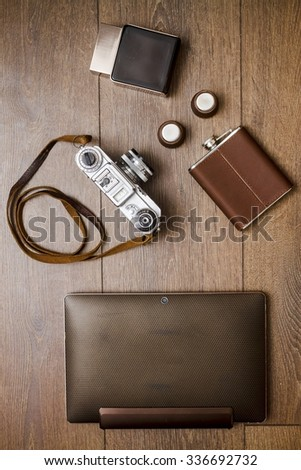 Vintage camera, perfume and leather belt on wooden floor - stock photo