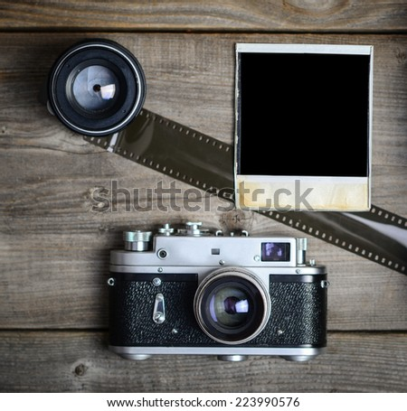 Vintage camera with lenses and blank old photograph on wooden background - stock photo