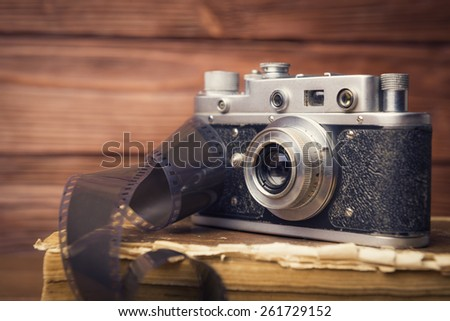 Vintage camera with 35mm film on old book over wooden defocused background - stock photo