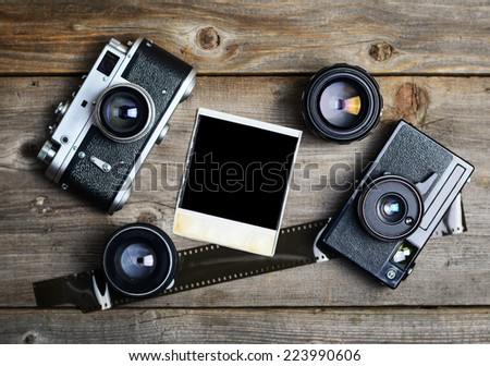 Vintage cameras around empty retro photograph on wooden background - stock photo