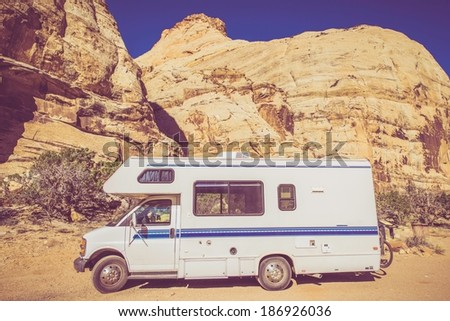 Vintage Camper in Utah Sandstone Canyon. Class C Recreation Vehicle. Vintage Color Grading. - stock photo