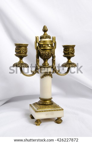 vintage candlestick for two candles with a quencher on the background of white cloth - stock photo