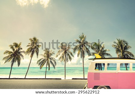 Vintage car in the beach with a surfboard on the roof - stock photo