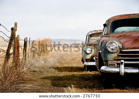 vintage cars abandoned and rusting away in rural wyoming - stock photo
