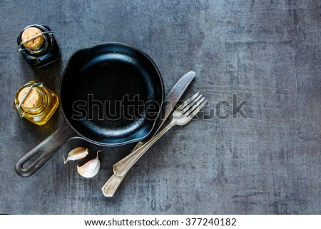 Vintage cast iron skillet with fresh garlic, olive oil and balsamic vinegar for tasty cooking on rustic background with space for text, top view, banner. Healthy food, vegan or diet nutrition concept. - stock photo