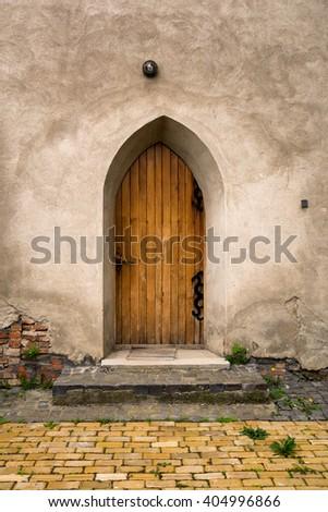 Vintage castle door and concrete wall - stock photo