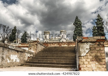 Vintage castle with stairs under cloudy sky - stock photo
