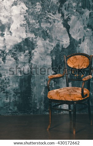Vintage chair on the background of shabby wall.  Cinema colour graded.
