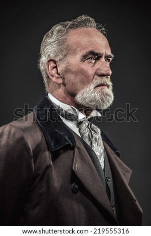 Vintage characteristic senior man with gray hair and beard. Studio shot against dark background. - stock photo