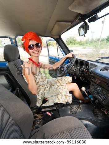 Vintage cheerful girl driving retro car and smiling