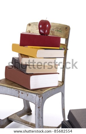 Vintage child's school chair holding a pile of books with an  apple and a pencil sitting beside a stack of hardbound books on the floor, all against a white background with a slight reflection. - stock photo