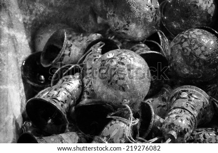 Vintage Christmas balls and bells decorated with flowers for sale at Christmas market. Old times idea. Retro aged photo with scratches. Black and white.