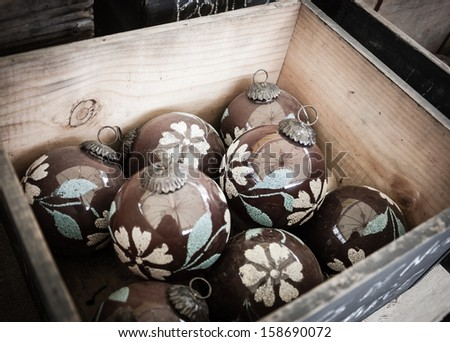 Vintage Christmas balls decorated with flowers in wooden box. Old times idea. Focus in remote ball. - stock photo