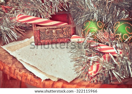 Vintage Christmas Ornament Background/ Christmas decorations red and white candy canes in old rustic wooden box on textured wooden background/ Composition with Brilliant Christmas decoration