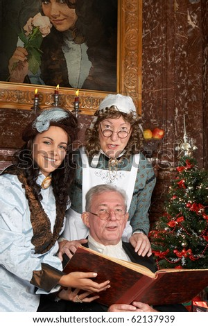 """Vintage christmas scene of a victorian family singing christmas carols. Shot in the antique castle """"Den Brandt"""" in Antwerp, Belgium (with signed property release for the Castle interiors). - stock photo"""