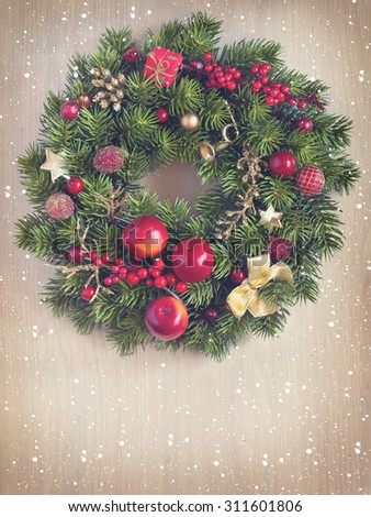 Vintage Christmas wreath hanging on old wooden background. Toned photo. - stock photo