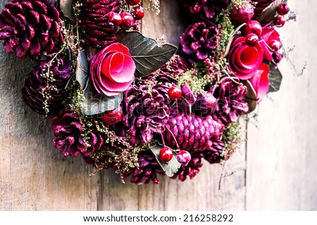 Vintage Christmas wreath with pine cones, flowers and red berries hanging on the grungy wooden door.  Greeting card.  - stock photo