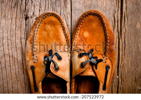 Vintage Classic Leather Brown Boat Shoes with Leather Lace Handmade Craftsmanship on Wood Stand Background, Rustic Still Life Style. - stock photo