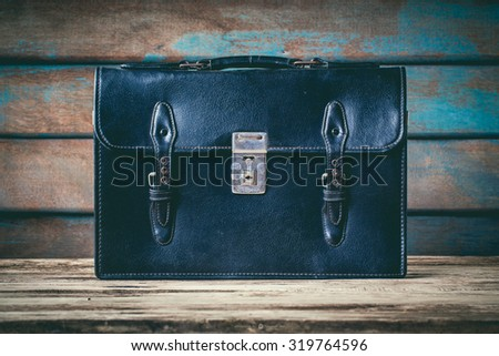 vintage classic of leather Schoolbag on wooden background. - stock photo