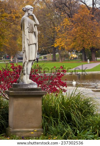 Vintage classical statue with autumnal leaves in public park - stock photo