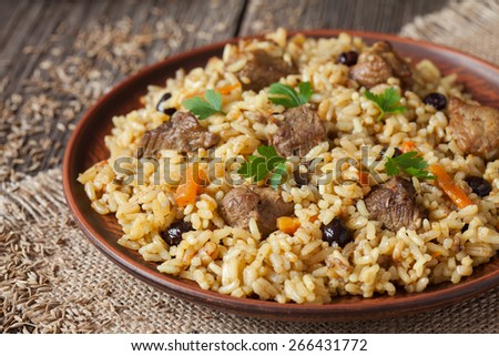 Vintage clay bowl with traditional spicy food called pilaf, on wooden background. Cooked with fried lamb, rice, garlic, carrot and raisins. - stock photo